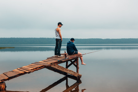 waits: Two men are waiting on a wooden bridge when the fish are biting. Weekend photo. Stock Photo