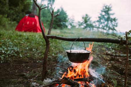 fish fire: Fish soup to cook on fire in nature. Outdoors photo.