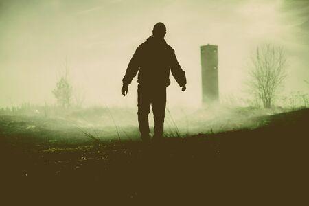 Silueta de la persona que camina y la torre. la noche foto.