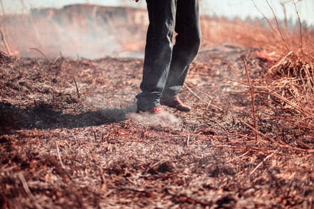 extinguish: Legs of the person extinguish fire. Outdoors photo.