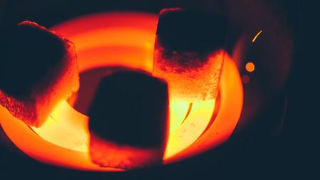 anochecer: carbón de coco cuadrado para pipa de agua en espiral al rojo vivo Foto de archivo