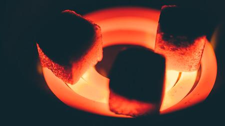 carbón de coco cuadrado para pipa de agua en espiral al rojo vivo Foto de archivo