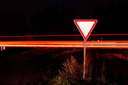 Road sign give way. Road sign at night on the background traffic at long exposure.