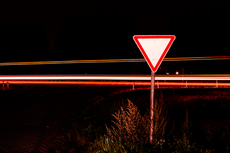 give the way: Road sign give way. Road sign at night on the background traffic at long exposure.