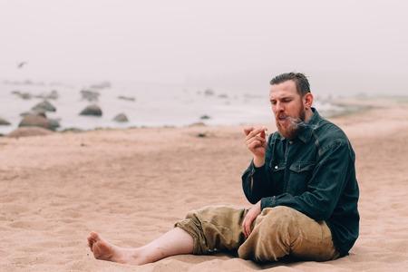 joven fumando: Hombre serio barbudo fumando un cigarrillo en la playa. inconformista barba en la playa