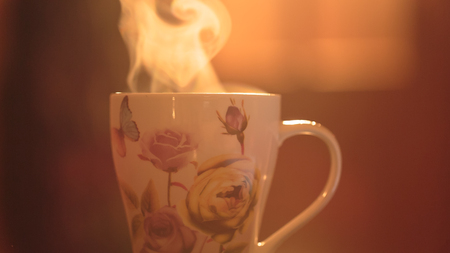 invigorating: Steam from the mug. Hot invigorating drink in a cup on a background of the early morning sun warm