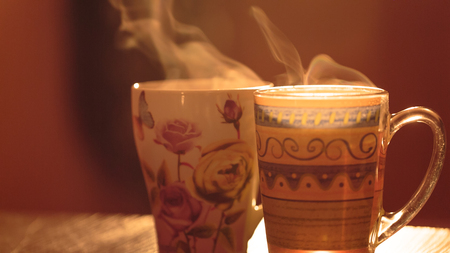 invigorating: Steam from the mugs. Hot invigorating drink in a cup on a background of the early morning sun warm