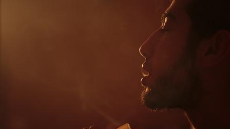 young bearded man smokes a hookah closeup Stock Photo