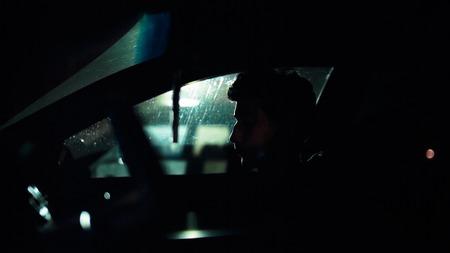 noir: Profile of a man in a car on a dark night. Noir style