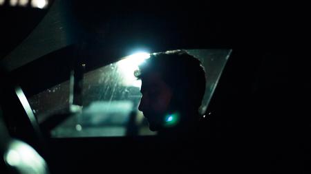 shadow man: Profile of a man in a car on a dark night. Noir style