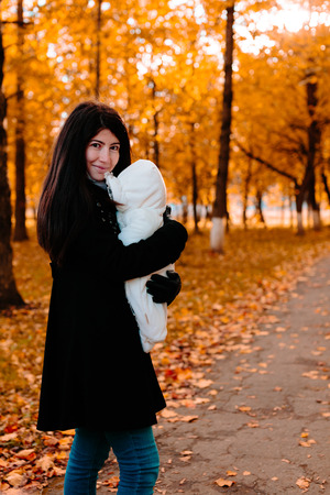 Young beautiful happy mother with her little baby on hand in autumn park Stock Photo