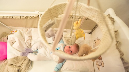 lying on his tummy: Baby lying in his cot and playing with Crib Mobiles. top view