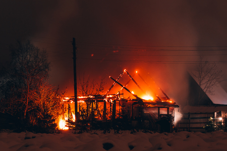 Burning wooden house in the winter night