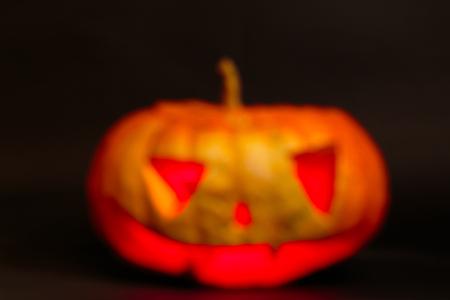 blurred jack o lantern big orange pumpkin on a black background
