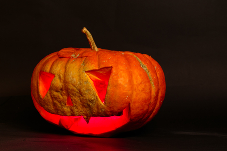 jack o lantern big orange pumpkin on a black background Stock Photo