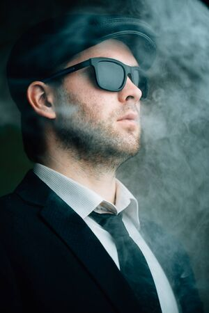 30 years old man: Fashionable male wearing sunglasses and a leather cap in the smoke