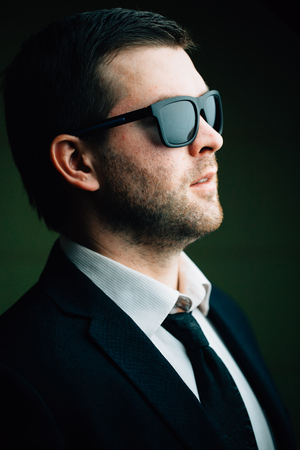 Portrait of a young trendy man in sunglasses in a dark room close up