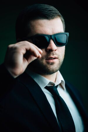 30 years old man: Portrait of a young trendy man in sunglasses lowered a little in the dark room close up
