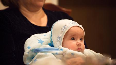 Piccolo bambino con la nonna sulle ginocchia a tavola