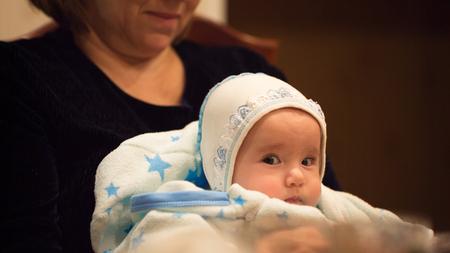 テーブルで彼の膝に彼の祖母の赤ちゃん 写真素材