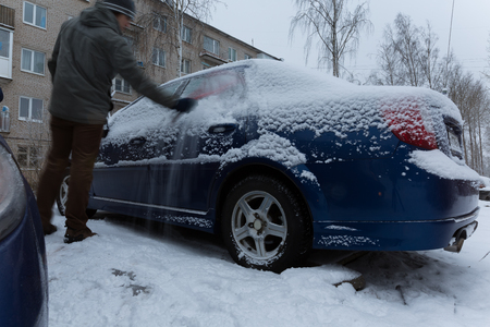 sweeps: Sweep snow from the car in winter timelapse. man sweeps the snow from his car in the parking lot Stock Photo