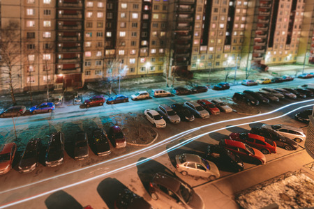 night shift: Car parking in the courtyard of apartment buildings at night Tilt Shift. miniature effect