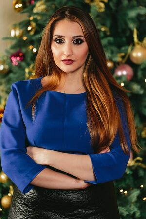 Beautiful girl on the background of the Christmas tree. Studio Vertical close-up portrait. Stock Photo