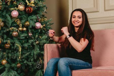 Beautiful young brunette woman smiling on a sofa near the Christmas tree. Studio horizontal portrait