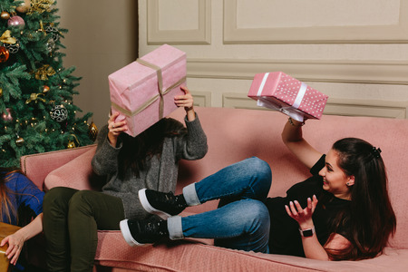 to unpack: beautiful young girls having fun gifts to share. studio horizontal Photo