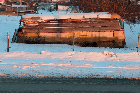 Old rusty and collapsed bus shrouded in snow. Photo in the daytime.