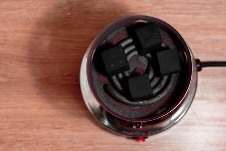 anochecer: Carbón de coco para cachimba en espiral caliente. Vista superior.