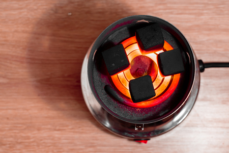 anochecer: Carbón de coco para cachimba en espiral rojo caliente. Vista superior. Foto de archivo