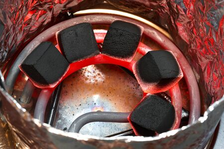 anochecer: Coconut charcoal for hookah on red hot spiral. Top view.