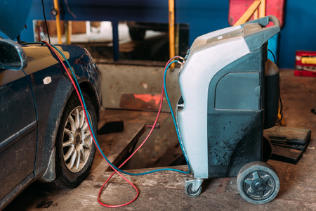 Equipment for the refueling of automobile air conditioner. Professional equipment in a workshop.