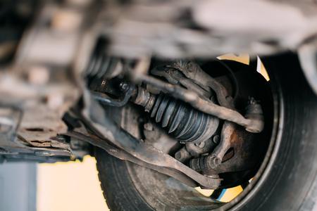 Car wheel bottom view. Garage mechanic raised the car on the lift. Stock Photo