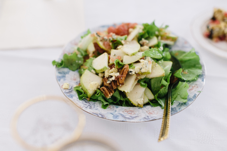 mayonesa: Ensalada en un plato sobre una mesa blanca. Foto de archivo
