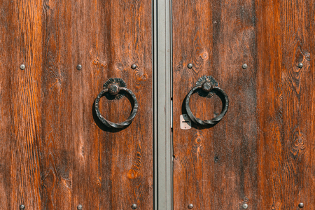 Wooden door with iron handles. Photo in the daytime.