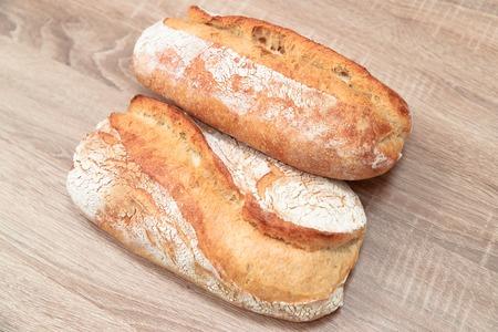 two tasty baked bread on a light wooden background Foto de archivo