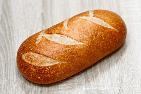 freshly baked loaf on a light wooden background