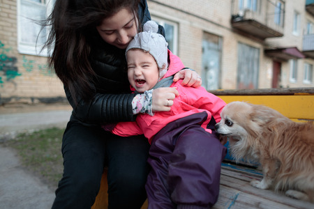 small and sweet girl with her mother and a fluffy dog