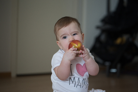 small child holds his hands apple and gnaws Stock Photo