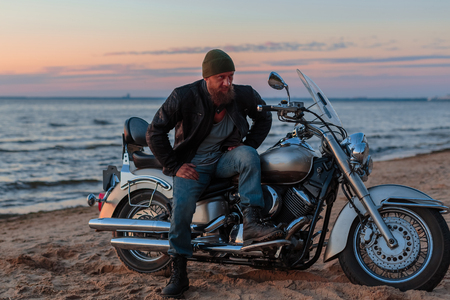 brutal man with a motorcycle on a sandy beach against the sea