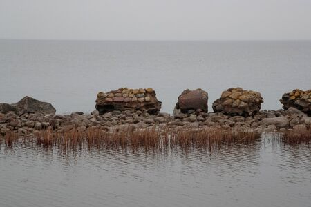 ruined stone fence surrounded by water in the sea
