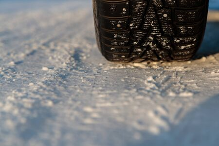 studded car wheel in winter on the road Stock Photo