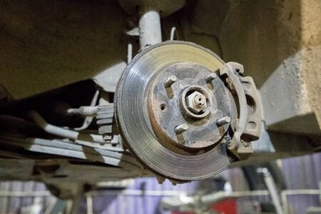 old and rusty brake disc of the car under repair in the garage Foto de archivo