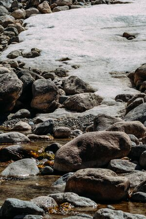 stones covered with snow and river movement. Imagens