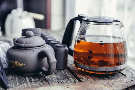 Chinese tea set and accessories made of yixing clay on an old wooden table