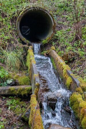 flow of the river through the old drain pipes in the forest in the autumn