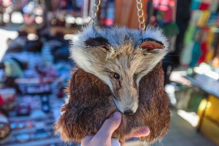 hand holds a bag in the form of a muzzle of a fox