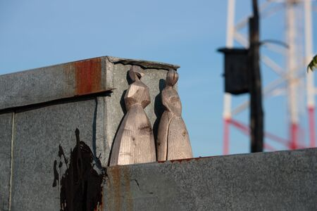 two figures in the form of girls in dresses carved from wood